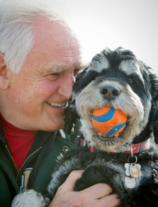 Garry-holding-his-best-friend-Oggie-the-portuguese-water-dog-cross-who-is-holding-is-orange-and-blue-ball